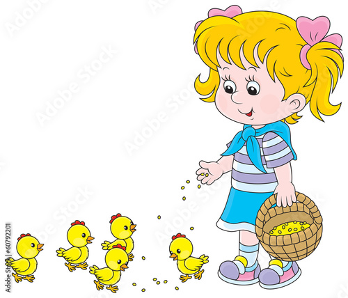 Little girl feeding small yellow chickens