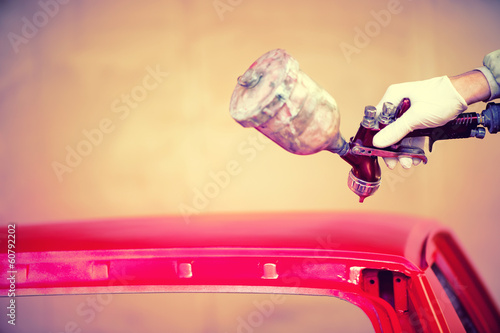 Worker hand painting a red hood of car in auto workshop