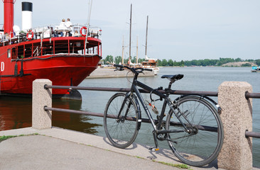 Pier with a bike and red steamship in Helsinki