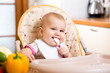 smiling baby girl eating food on kitchen
