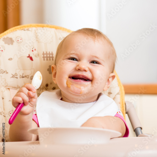 smiling baby eating food on kitchen
