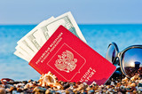 passport with money and sunglasses on the beach