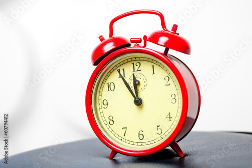 red alarm clock in a retro style shot in a studio