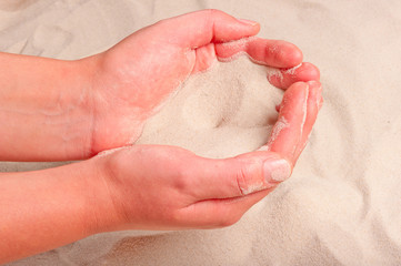 fine sand flowing out of women's hands