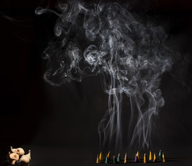 Burning incense cones with intense smoke on black background
