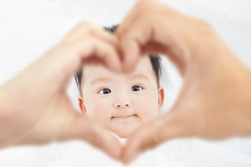 cute and smiling infant  with parents love hands