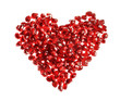 Red heart made of pomegranate seeds on white background