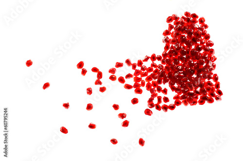 Red broken heart made of pomegranate seeds on white background