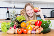 Junge frau sitzt vor einem Berg Gemüse und Obst