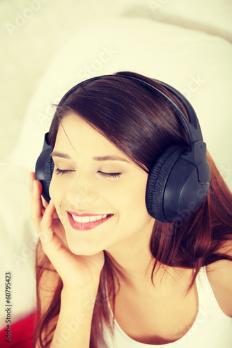 Young beautiful woman at home listening music