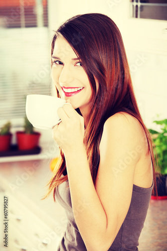 Beautiful woman in the kitchen drinking something