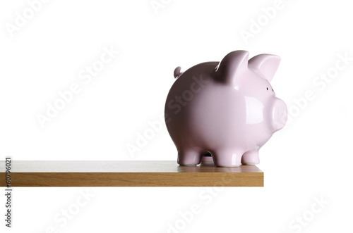 Piggy bank placed close to the edge of a board