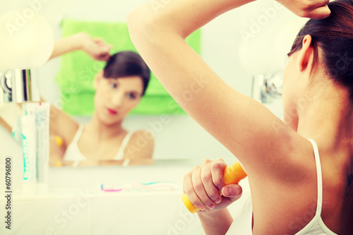 Young beautiful caucasian woman using deodorant