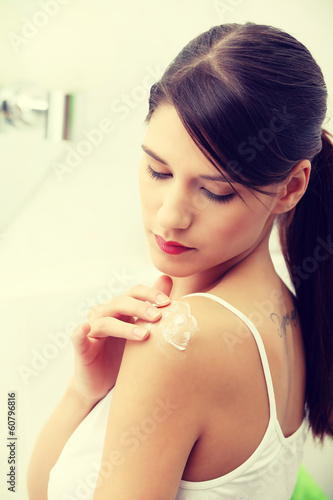 Woman applying cream on shoulder.