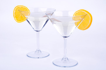 two glasses of martini and lemon on blue