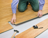 Man laying laminated panels color of wood