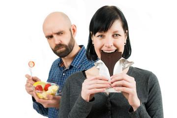 Mann mit Obstschale schaut wütend zu seiner Frau