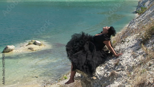 Woman dressed in black resting on a shore of a lake