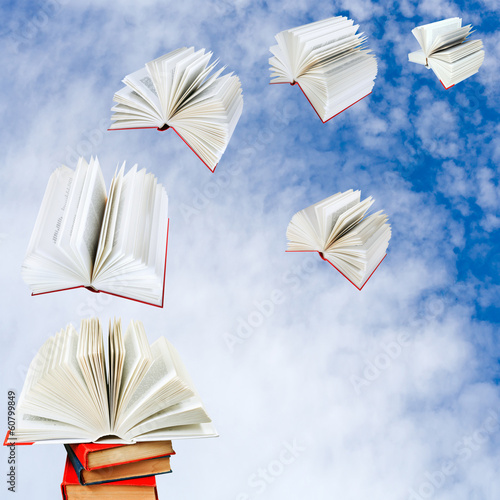 books fly out of pile of books - 60799849