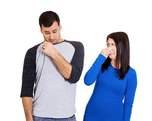 Woman smells bad odor looking at man who sniffs himself