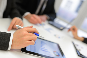 Business team using tablet computer to work with financial data