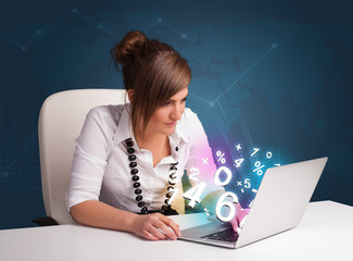 Beautiful young woman sitting at desk and typing on laptop with