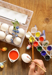 Coloring Easter eggs (hand in the shot)  paint and brushes