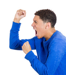 Angry, aggressive young man with fists in air, screaming