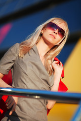Blond woman in sunglasses against office windows