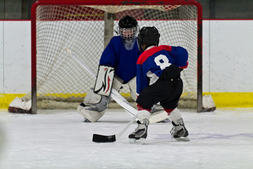 Young ice hockey player prepares to shoot on net
