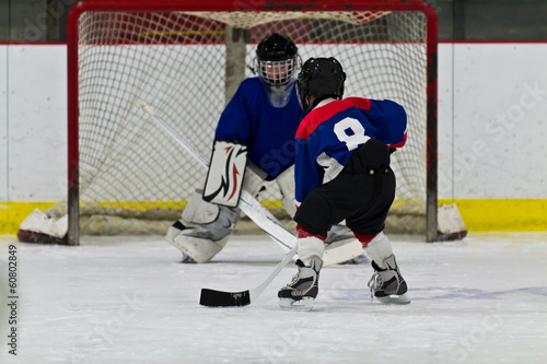 Foto op Canvas Wintersporten Young ice hockey player prepares to shoot on net
