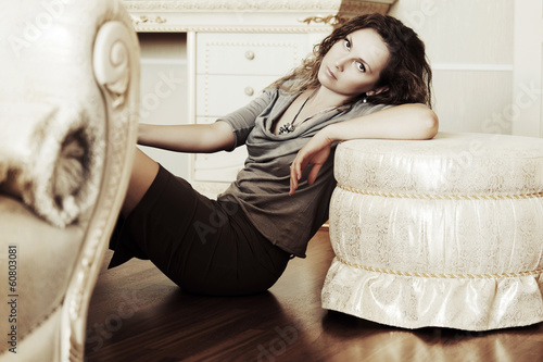 Sad beautiful woman sitting on the floor at apartment