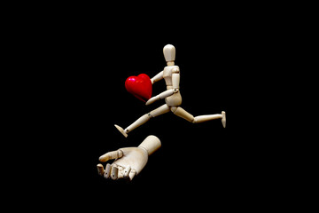 A mannequin with a red heart and jumping over a wooden hand