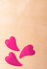 three red hearts on a wooden  board