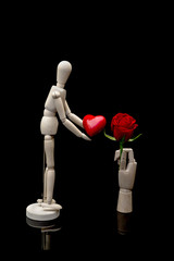 Two wooden mannequins holding red heart and red rose