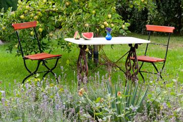 Klassische Gartenmöbel in einem sommerlichen Garten