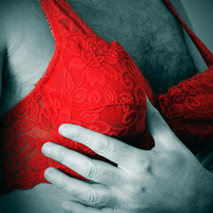 a man wearing a red lace bra