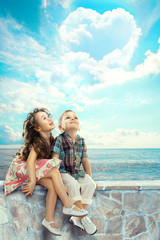 Children looking blue sky with heart shaped clouds