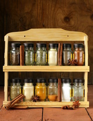 different set of spices in glass jars on wooden shelf