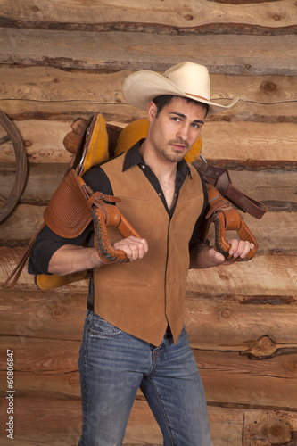 man with a saddle on his back cowboy hat