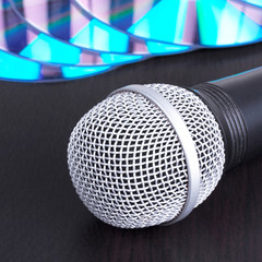Microphone and compact disks on black table