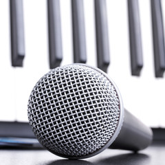 Microphone and piano keyboard on black table