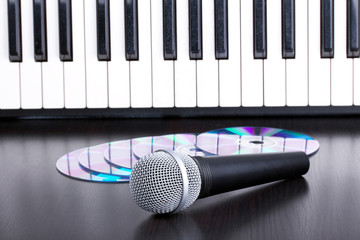 Microphone, cd and piano keyboard on black table