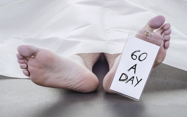 smoker, feet of a deceased man with toe tag that reads 60 a day