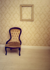 Antique upholstered chair in a wallpapered room