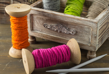 Spools of colorful wool yarn and knitting needles