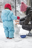 Mother and child building a winter snowman