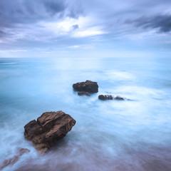 Rocks in a ocean waves under cloudy sky. Bad weather.