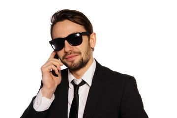Smiling businessman in sunglasses on his mobile