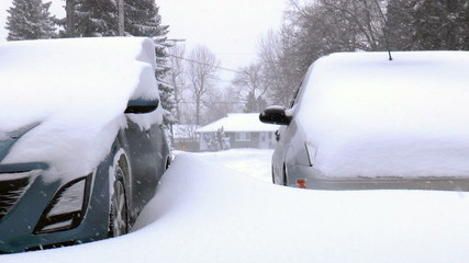 Two cars covered by snow, under severe winter storm.